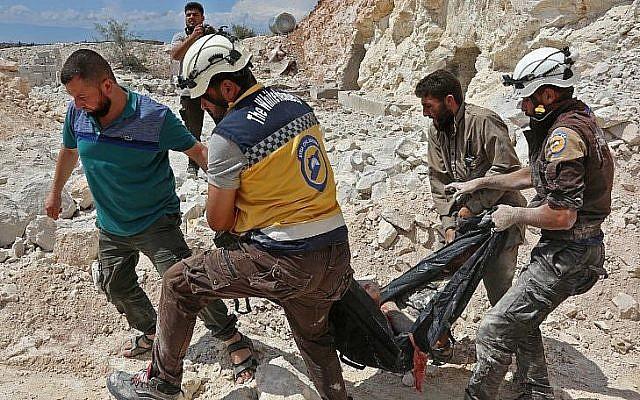 A Kafr Ain, des membres de la Défense civile syrienne, connus sous le nom de Casques blancs, transportent une victime après des frappes aériennes à 4 kilomètres à l'est de Khan Shaykhun idans le sud de la province d'Dlib, le 7 septembre 2018 (Crédit : AFP PHOTO / Anas AL-DYAB)