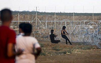 Les Palestiniens tirent un câble attaché à un fil barbelé pour essayer de détruire une section de la clôture de sécurité entre la bande de Gaza et Israël, durant des affrontements survenus à l'est de Gaza City, le 7 septembre 2018 (Crédit : AFP/Said Khatib)