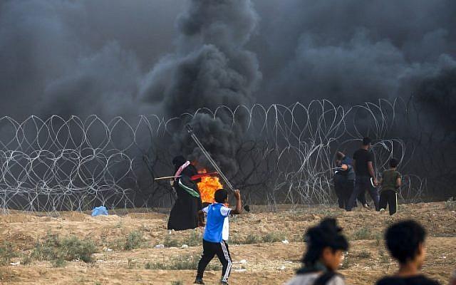 Un jeune Palestinien utilise une fronde pour jeter des pierres aux forces israéliennes durant des affrontements à la frontière entre Israël et la bande de Gaza, à l'est de Gaza city, le 7 septembre 2018 (Crédit : AFP/Said Khatib)