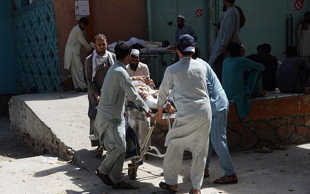 Des volontaires et des parents afghans transportent une victime blessée sur une civière pour qu'elle reçoive des soins médicaux au Pakistan le lendemain d'un attentat-suicide visant des manifestants dans le district de Mohmand Dara de la province de Nangarhar, à Jalalalabad, le 12 septembre 2018. (AFP PHOTO / NOORULLAH SHIRZADA)