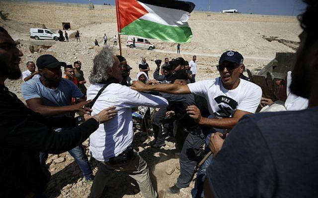 Les forces de sécurité israéliennes se bagarrent avec le manifestant franco-américain Frank Romano, le 14 septembre 2018, durant une manifestation contre la destruction du village bédouin de Khan al-Ahmar, en Cisjordanie (Crédit : AFP PHOTO / ABBAS MOMANI)