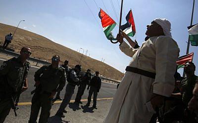 Des manifestants palestiniens brandissent le drapeau national devant les soldats israéliens pendant une manifestation contre le plan de démolition israélien du village bédouin de Khan al-Ahmar, en Cisjordanie, le 14 septembre 2018 (Crédit :AFP PHOTO / ABBAS MOMANI)