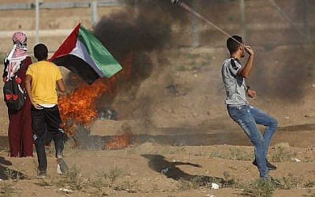 Un manifestant palestinien utilise un lance-pierre alors que d'autres se tiennent près d'un pneu en flammes et agitent un drapeau national lors d'une manifestation le long de la clôture de la frontière à l'est de Gaza le 14 septembre 2018. (AFP PHOTO / Said KHATIB)