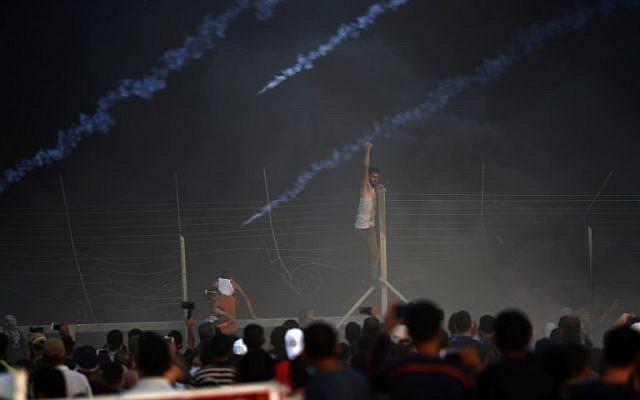 Un manifestant palestinien grimpe sur une clôture au cours d'une manifestation nocturne le long de la frontière entre Israël et Gaza parmi les fumées des pneus brûlés et les gaz lacrymogènes, le 14 septembre 2018 (Crédit :  / AFP PHOTO / Said KHATIB)