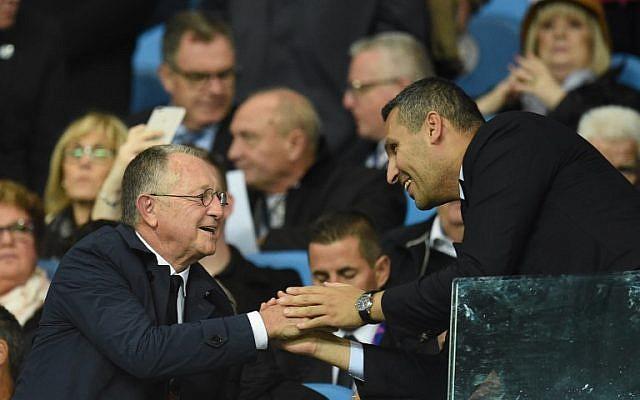 Le président lyonnais Jean-Michel Aulas (à gauche) accueille Khaldoon Al Mubarak, président de Manchester City, avant le match de football du groupe F de l'UEFA Champions League entre Manchester City et Lyon au stade Etihad à Manchester, au nord-ouest de l'Angleterre, le 19 septembre 2018. (AFP PHOTO / Oli SCARFF)