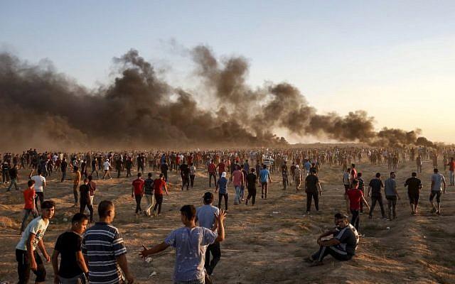 Des manifestants palestiniens rassemblés le long de la barrière frontalière israélienne à l'est de la ville de Gaza, alors que de la fumée émane de pneus, le 21 septembre 2018. (AFP / Said Khatib)
