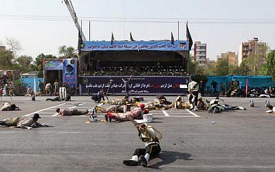 Des soldats blessés au sol sur la scène d'un attentat survenu pendant une parade militaire marquant l'anniversaire de la guerre de 1980-1988 avec l'Irak de Saddam Hussein, le 22 septembre 2018 (Crédit :  / AFP PHOTO / ISNA / ALIREZA MOHAMMADI)