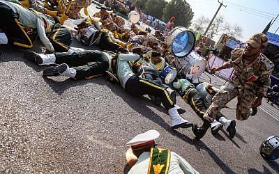 Un soldat iranien court devant ses collègues blessés, au sol, lors d'une attaque contre une parade militaire à Ahvaz, le 22 septembre 2018 (Crédit : AFP/ ISNA / MORTEZA JABERIAN)