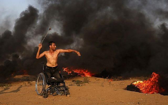 Un manifestant palestinien sur une chaise roulante jette une pierre vers les forces israéliennes durant des affrontements sur la clôture frontalière avec Gaza, à l'est de Gaza City, le 28 septembre 2018 (Crédit : / AFP PHOTO / Said KHATIB)