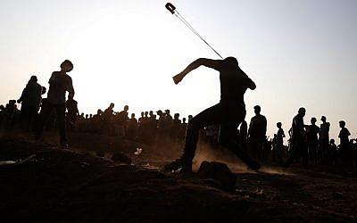 Un manifestant palestinien jette une pierre vers les soldats israéliens pendant des affrontements le long de la frontière de Gaza, le 28 septembre 2018 (Crédit :. / AFP PHOTO / Said KHATIB)