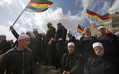 Des Druzes sur le plateau du Golan se réunissent sur la frontière syrienne en brandissant le drapeau de la communauté après un attentat kamikaze à la bombe dans le village druze syrien de Hadar, le 3 novembre 2017 (Crédit : AFP PHOTO / JALAA MAREY)