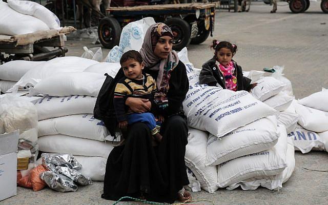 Une femme palestinienne avec ses enfants après avoir reçu des vivres au camp de réfugiés de Khan Younis, dans le sud de la bande de Gaza, le 11 février 2018. (AFP / Said Khatib)