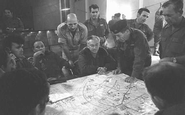 Les membres de l'état-major regardent une carte pendant l'éclatement de la guerre de Yom Kippour, le 17 octobre 1973 (Crédit : Bamahane/Archives du ministère de la Défense)