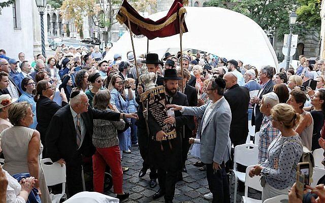 Le rabbin Asher Faith transporte un rouleau de Torah tout juste consacré pour la congrégation, lors de la consécration de l'espace de prière de la synagogue médiévale de Budapest, le 6 septembre 2018 (Crédit : Márton Merész)