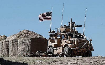 Un soldat américain assis sur un véhicule blindé à un nouveau poste de Manbij,  au nord de la Syrie, le 4 avril 2018 (Crédit : Hussein Malla/AP)