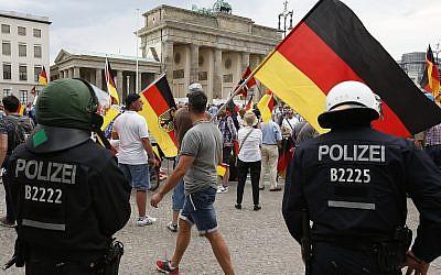 Les partisans de l'AfD allemande brandissent des drapeaux devant la porte de Brandenburg à Berlin, en Allemagne, le 27 mai 2018 (Crédit :  AP Photo/Michael Sohn)