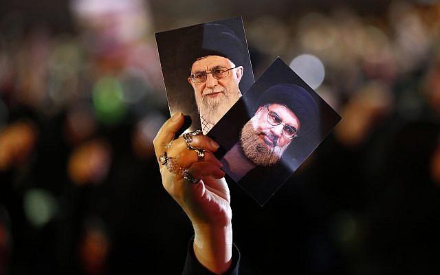 Un partisan du Hezbollah tient des portraits du sheikh Hassan Nasrallah du Hezbollah,  à droite, et du chef suprême iranien, l'Ayatollah Ali Khamenei, à gauche, durant des activités marquant l'Achoura, commémorant pendant 10 jours la mort de l'Imam Hussein, dans un quartier du sud de Beyrouth, au Liban (Crédit : AP Photo/Hussein Malla)
