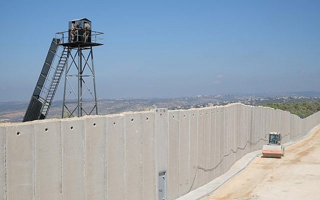 """Un véhicule de construction israélien passe à côté d'un mur de béton en construction le long de la """"Ligne bleue"""" séparant Israël et le Liban, alors que des membres des Forces armées libanaises observent depuis une tour de garde, près de la ville israélienne de Rosh Hanikra, le 5 septembre 2018. (Judah Ari Gross/Times of Israel)"""