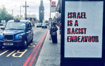 """Un arrête de bus à Londres vandalisé avec une affiche  """"Israel is a racist endeavor"""" (Israël est une entreprise raciste), pour protester contre l'adoption, par le parti travailliste britannique, de la définition de l'antisémitisme internationale, qui considère cette phrase comme antisémite, le 6 septembre 2018. (Crédit : Twitter)"""