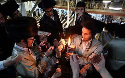 Des ultra-orthodoxes allument la'Havdallah'  qui marque la fin du Shabbat juif dans une synagogue d'Ouman, en Ukraine, pendant la fête juive de Rosh HaShana, le 7 septembre 2013 (Crédit : Yaakov Naumi/Flash90)