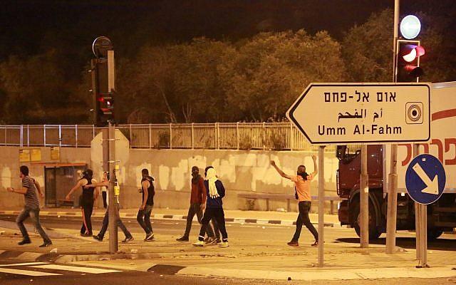 Des manifestants jettent des pierres aux forces de sécurité israéliennes, non visibles, à Umm el Fahm, le 5 juillet 2014 (Crédit :Omar Samir/FLASH90)