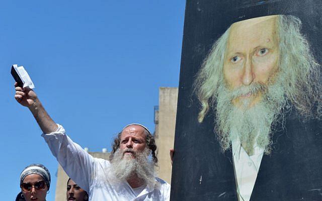 Des hommes se rassemblent pour prier lors d'une manifestation de soutien à Eliezer Berland devant le tribunal de Lod, dans le centre d'Israël, le 26 juillet 2016. (Crédit : Avi Dishi/Flash90)