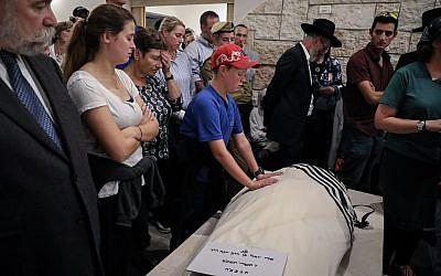 Le fils d'Ari Fuld place ses mains sur le corps de son père pendant ses funérailles à Kfar Etzion, le 17 septembre 2018 (Crédit : Gershon Elinson/FLASH90)