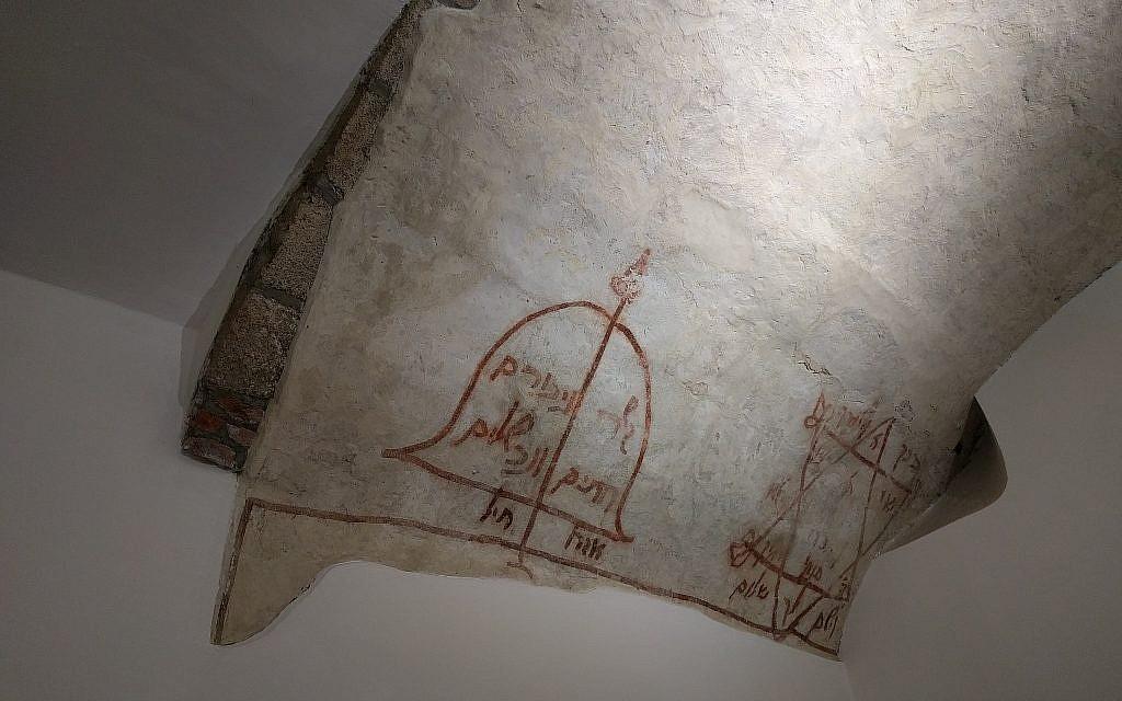Des inscriptions en hébreu sur le plafond de la synagogue médiévale montrent un arc et une flèche avec une prière pour la paix et une étoile de David avec une bénédiction rabbinique (Crédit : Yaakov Schwartz/ Times of Israel)
