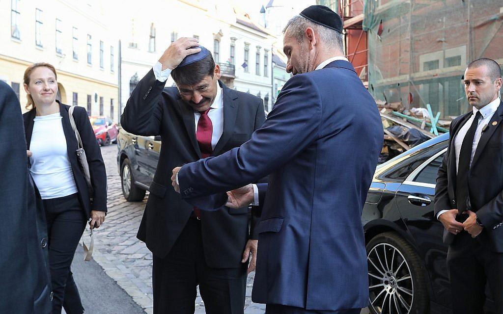 Le président hongrois Janos Ader met une kippa lors de la consécration de l'espace de prière de la synagogue médiévale à Budapest, le 6 septembre 2018 (Crédit : Márton Merész)