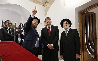 Le rabbin Slomo Koves, président de l'EMIH, à gauche, avec le président hongrois Janos Ader, au centre, et le grand rabbin de Hollande, Benjamin Jacobs, examinent les inscriptions au plafond de la synagogue médiévale à Budapest, le 6 septembre 2018 (Crédit : Márton Merész)