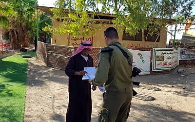 Le 23 septembre 2018, un fonctionnaire de l'administration civile remet à l'un de ses résidents un avis concernant la démolition imminente de Khan al-Ahmar (Crédit : Administration civile).