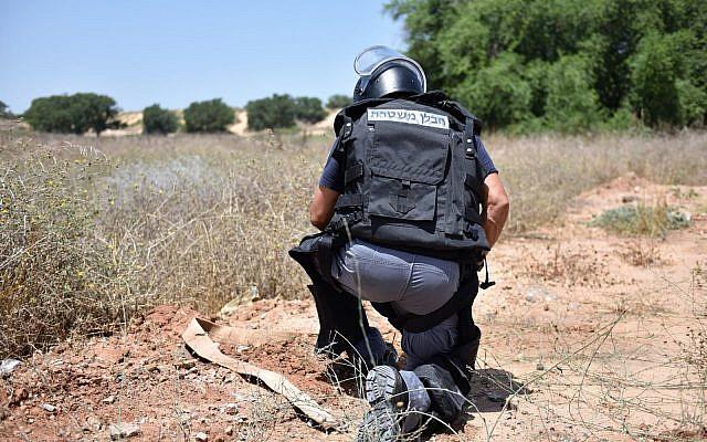 Un sapeur de la police désarme un dispositif explosif aérien qui a atterri dans la ville de   Kiryat Gat, au sud d'Israël, le 14 septembre 2018 (Crédit : Police israélienne)