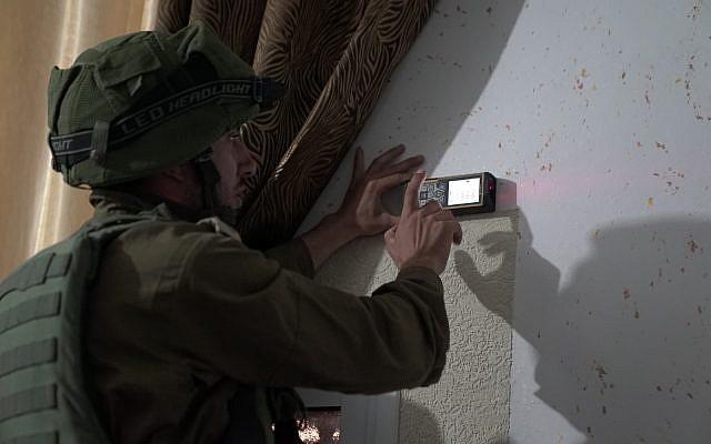Les soldats israéliens mesurent l'habitation d'un terroriste palestinien qui a mortellement poignardé un Israélien afin de préparer la construction de sa démolition dans le village de Cisjordanie de Yatta, à côté de Hébron, le 17 septembre 2018 (Crédit : Armée israélienne)
