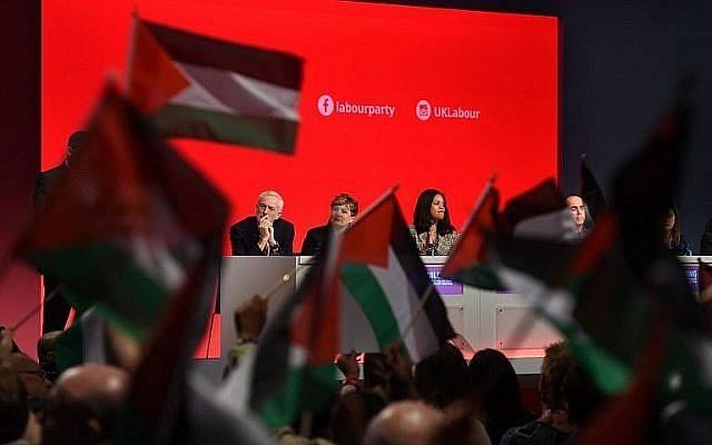 Les participants à la conférence du parti travailliste à Liverpool ont brandi des drapeaux palestiniens lors d'un débat, le 25 septembre 2018, alors que le leader Jeremy Corbyn est installé à la tribune. (Crédit : AFP Photo / Oli Scarff)