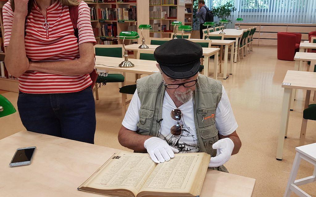 Yoram Sztykgold examine l'annuaire de 1939 qui l'a aidé à localiser les biens de sa famille dans une librairie de Varsovie, le 4 septembre 2018 (Crédit : Cnaan Liphshiz)