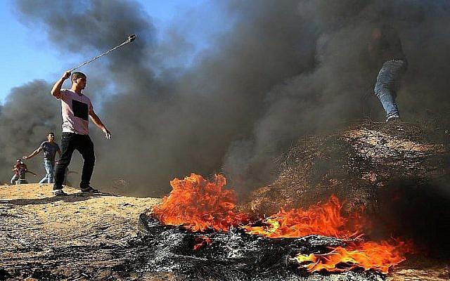 Un Palestinien avec un lance-pierres à côté de pneus brûlés lors d'affrontements à la frontière entre Israël et Gaza, à l'est de Khan Yunis, dans le sud de la bande de Gaza, le 10 août 2018. (AFP / Said Khatib)
