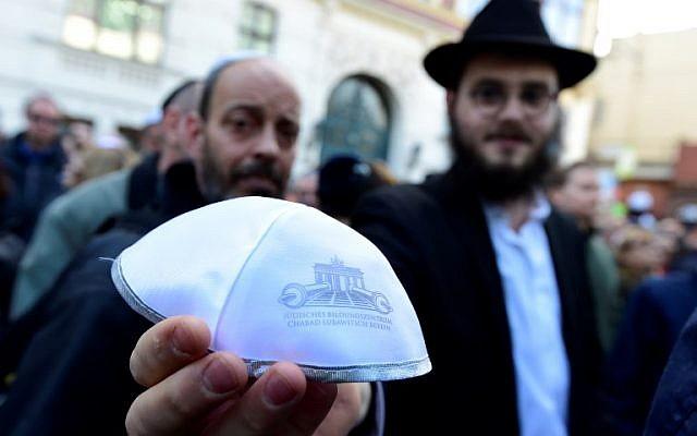 """Photo d'illustration : Un homme montre une kippa pendant l'événement """"Berlin porte une kippa"""" qui a attiré plus de 2000 Juifs et non-Juifs en signe de solidarité à Berlin, le 25 avril 2018 (Crédit : AFP/Tobias Schwartz)"""