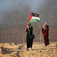Une Palestinienne porte son drapeau national lors d'une manifestation pour la levée du blocus israélien de Gaza sur une plage à Beit Lahia près de la frontière maritime avec Israël, le 17 septembre 2018. (Crédit : AFP PHOTO / Said KHATIB)
