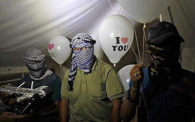 """Des Palestiniens cagoulés qui se font appelé 'l'unité de la confusion de la nuit"""" tiennent des dispositifs incendiaires attachés à des ballons qui vont être lancés en Israël, depuis Rafah, le 26 septembre 2018. (Crédit : AFP /Said Khatib)"""
