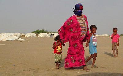 La mère d'Imad, à droite, et d'Alia, à gauche, leur tient la main alors qu'ils marchent dans le camp d' al-Waara, dans le district de Khokha, à environ 30 kilomètres de la ville de Hays, le 1er octobre 2018 (Crédit :  / AFP PHOTO / NABIL HASSAN