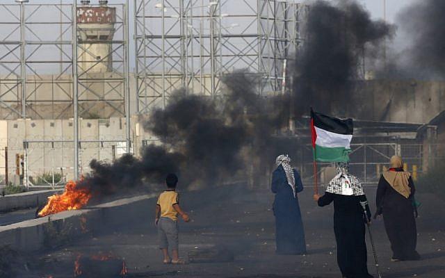 Une Palestinienne porte un drapeau lors d'une manifestation au poste frontière d'Erez avec Israël dans le nord de la bande de Gaza, le 3 octobre 2018. (AFP/ Said KHATIB)