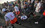 Des ambulanciers palestiniens transportent un homme blessé lors d'une manifestation au poste frontière d'Erez avec Israël, dans le nord de la bande de Gaza, le 3 octobre 2018. (AFP/Said Khatib)