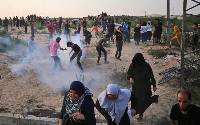 Des Palestiniens manifestent dans des fumées de gaz lacrymogène au poste frontière d'Erez avec Israël dans le nord de la bande de Gaza le 3 octobre 2018. (AFP PHOTO / DIT KHATIB)