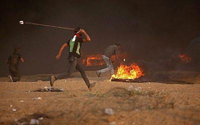 Un Palestinien jette une pierre vers les soldats israéliens durant des affrontements le long de la frontière entre la bande de Gaza et Israël à l'est de Gaza City, le 5 octobre 2018 (Crédit :  AFP Photo/Said Khatib)