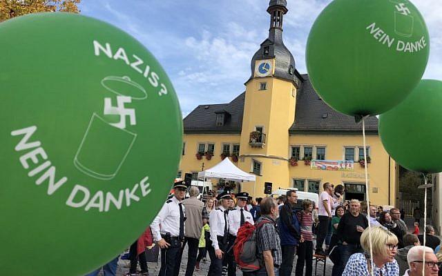 """Des manifestants munis de ballons sur lesquels on peut lire """"Nazis, non merci"""", à un concert de rock à Apolda, le 6 octobre 2018. (Crédit ! AFP PHOTO / dpa / Sebastian Haak)"""