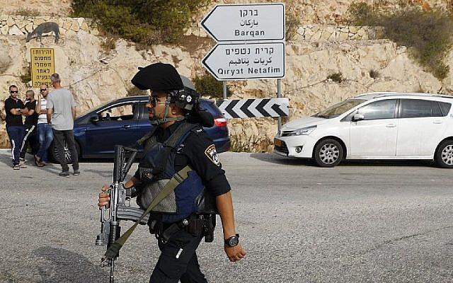 Les forces de sécurité israéliennes sur le site d'un attentat terroriste au parc industriel Barkan, à proximité de l'implantation d'Ariel, dans le nord de la Cisjordanie, le 7 octobre 2018 (Crédit : AFP Photo/Jack Guez)