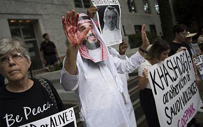 Un manifestant déguisé en prince saoudien Mohammed bin Salman (C), le visage ensanglanté, manifestait devant les locaux de l'ambassade saoudienne à Washington, le 8 octobre 2018, pour demander que justice soit rendue pour le journaliste égaré Jamal Khashoggi. (Crédit : Jim Watson / AFP)