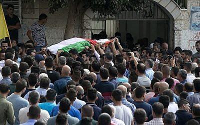 Des Palestiniens transportent le corps d'Aisha Rabi, mère de huit enfants, 48 ans, morte de ses blessures après que sa voiture a fait l'objet d'un caillassage, pendant ses funérailles à Biddya, en Cisjordanie, le 13 octobre 2018 (Crédit : JAAFAR ASHTIYEH / AFP)