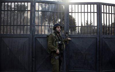 Un soldat israélien monte la garde devant une école palestinienne fermée par Israël, en Cisjordanie, le 16 octobre 2018. (Crédit : JAAFAR ASHTIYEH / AFP)