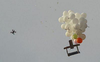Cette photo prise au Kibbutz Nahal Oz dans le sud d'Israël montre un drone militaire israélien s'approcher de ballons transportant un dispositif incendiaire lancé depuis la bande de Gaza, le 18 octobre 2018 (Crédit : Jack Guez/AFP)